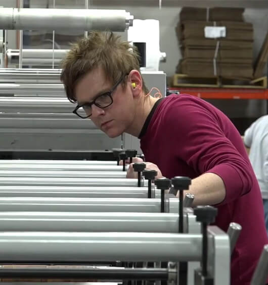 An Apogee employee examines printing equipment
